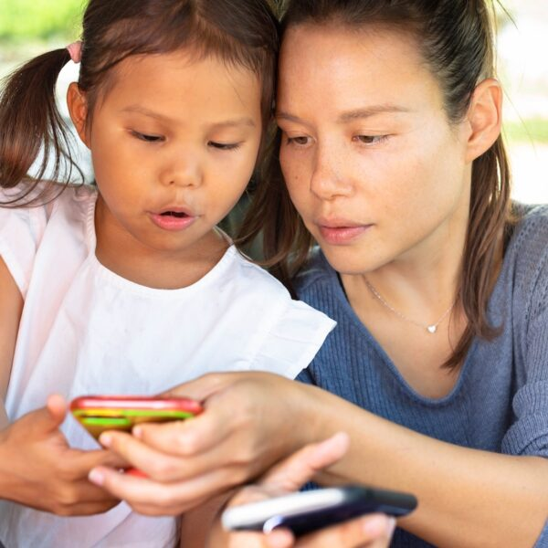 Mother and daughter look at mobile phones